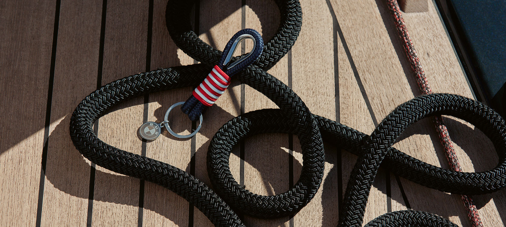 A BMW Yachtsport Keyring from the BMW Yachtsport Collection is shown lying on wooden decking.