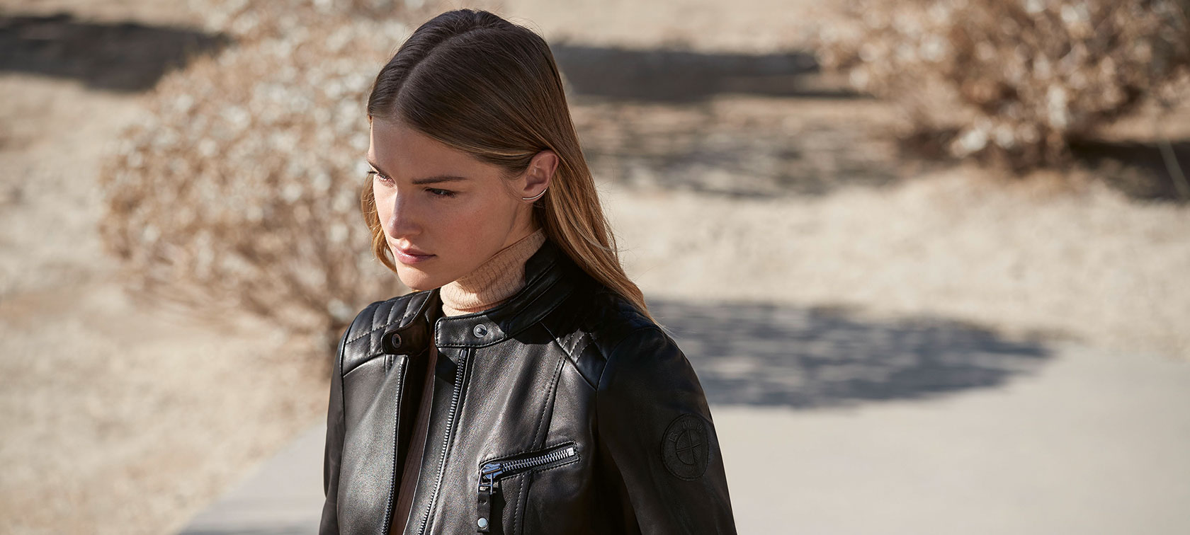 A female model is wearing the BMW Leather Jacket for ladies.