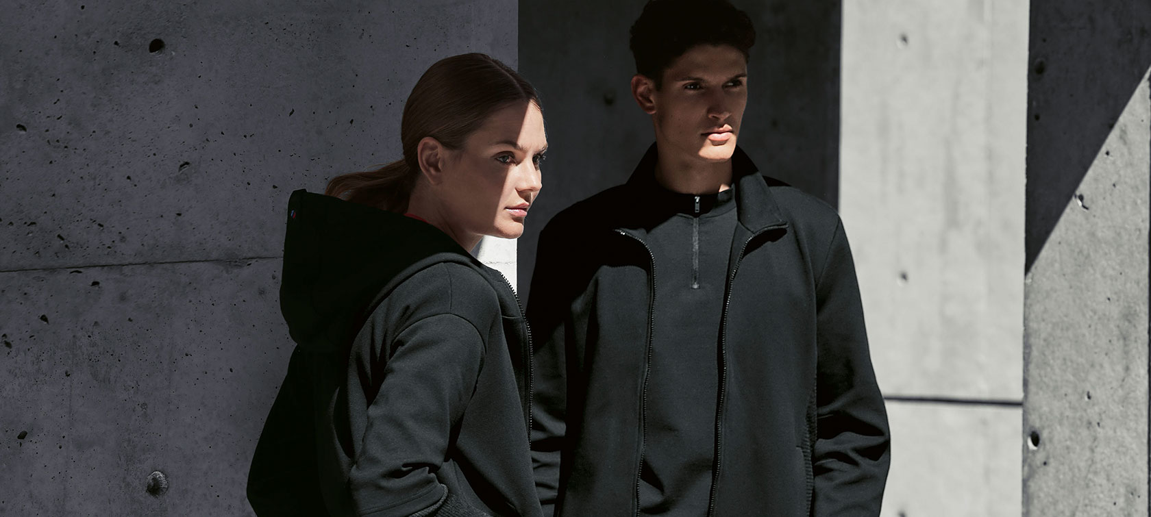 A couple is standing in the shadow. A woman is presenting the BMW M Sweat Jacket for ladies and a man is wearing the BMW M Sweat Jacket for men.